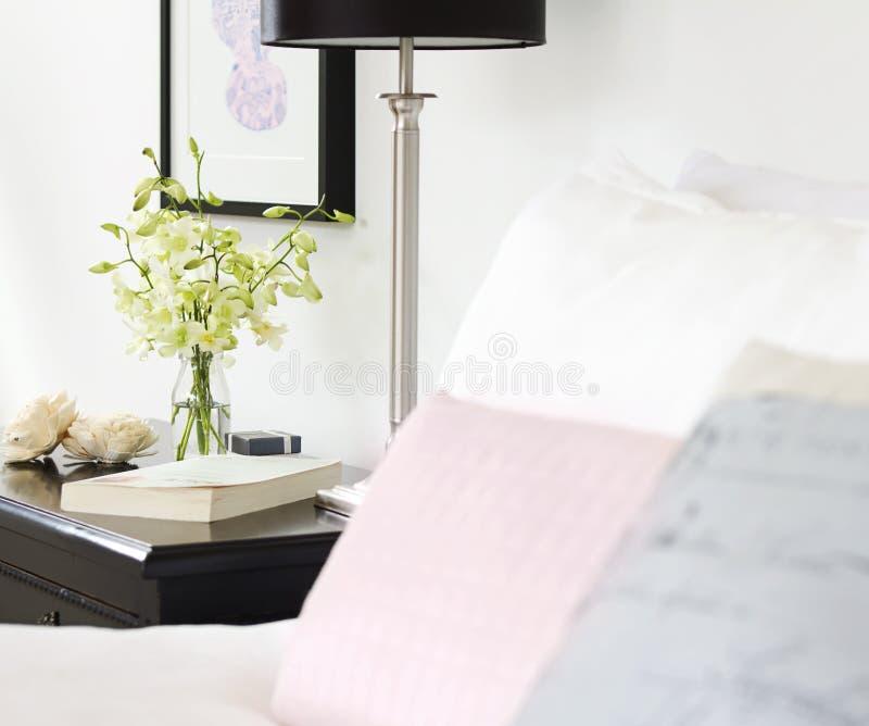 在花瓶的兰花在与文本空间的俏丽的床头柜上 库存照片