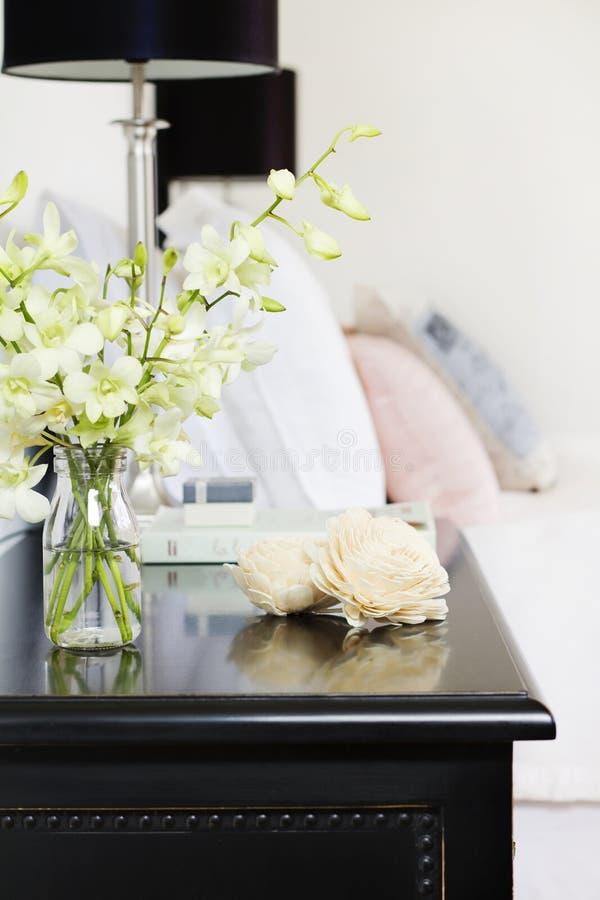 在花瓶的兰花在俏丽的床头柜垂直 库存图片