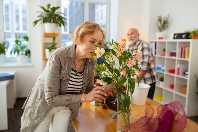在花瓶的快乐的年迈的妇女嗅到的花 库存照片