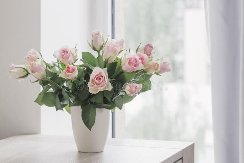 在花瓶的桃红色玫瑰在背景窗口 图库摄影