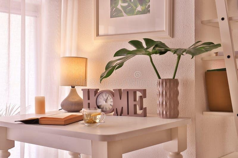 在花瓶的热带叶子有装饰时钟和开放书的在桌上在屋子里 库存图片
