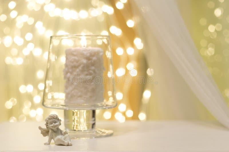 在花瓶的燃烧的蜡烛有在它旁边的一个天使形象的 免版税图库摄影