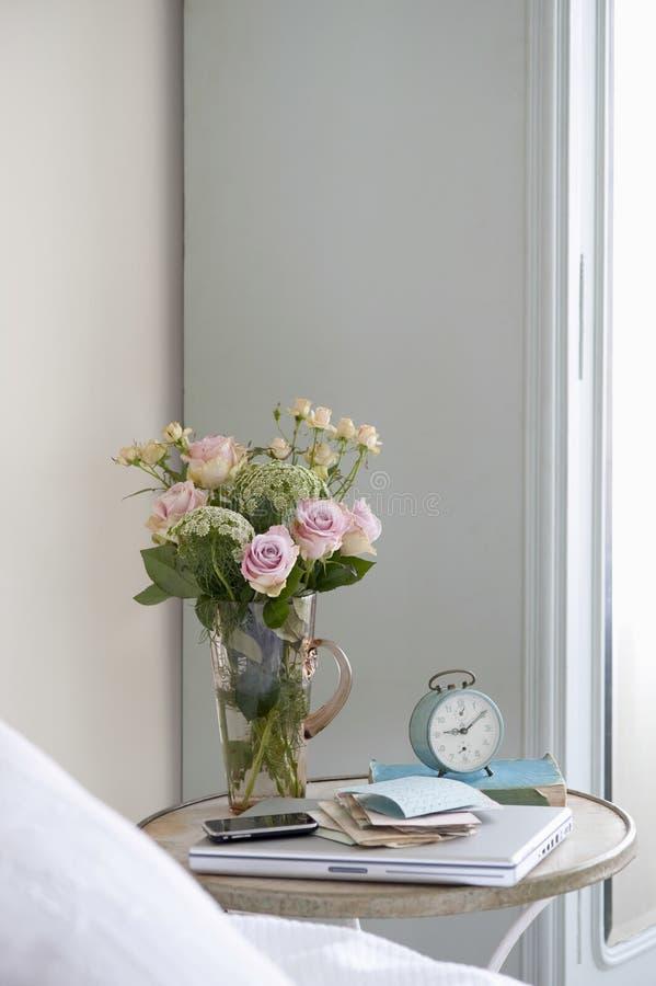 在花瓶的玫瑰在床头柜上 免版税库存照片