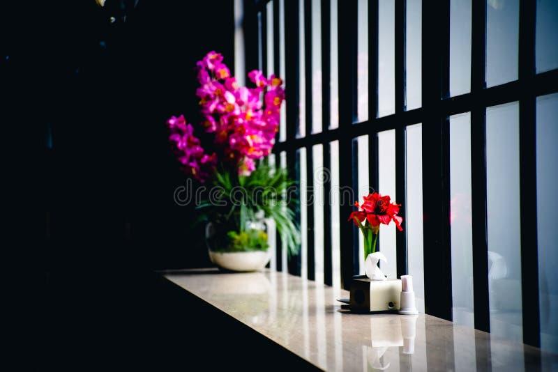 在花瓶的美丽的紫色和红色花在窗台 免版税库存图片