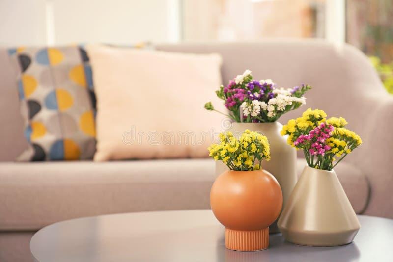 在花瓶的美丽的花作为室内设计的元素在桌上的 库存图片