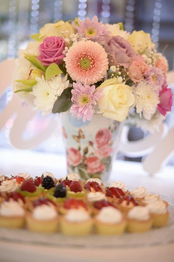 在花瓶的美丽的花花束用在桌上的可口杯形蛋糕 图库摄影