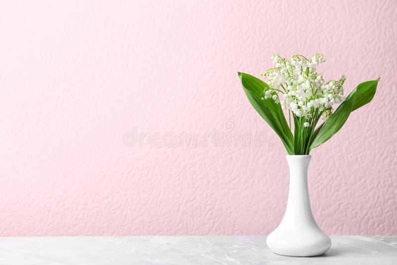在花瓶的美丽的铃兰花束在颜色墙壁附近的桌上 库存图片