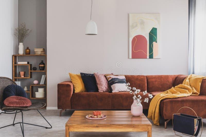 在花瓶的花在木咖啡桌上在时兴的客厅内部与有枕头和摘要的棕色壁角沙发 免版税库存图片