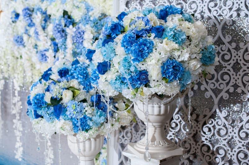 在花瓶的花站立Decorate的设置用婚礼背景 图库摄影