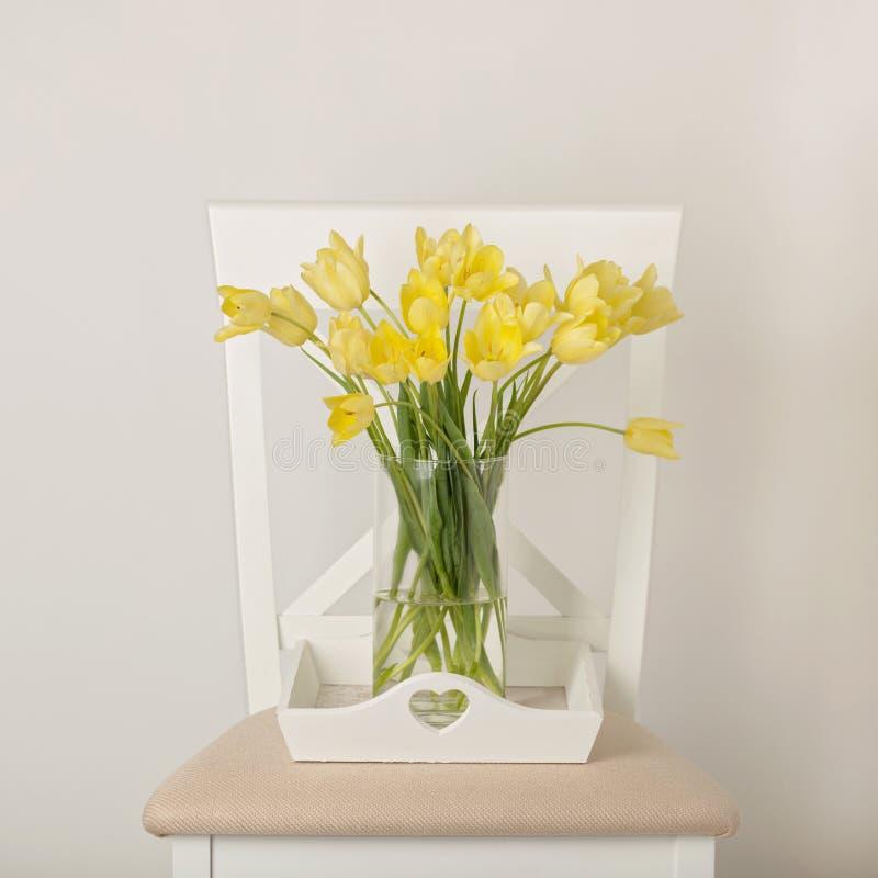 在花瓶的黄色郁金香在椅子的白色盘子 免版税库存图片
