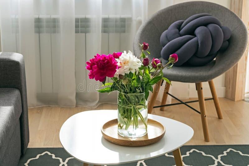 在花瓶身分的牡丹在小桌上在客厅 免版税图库摄影