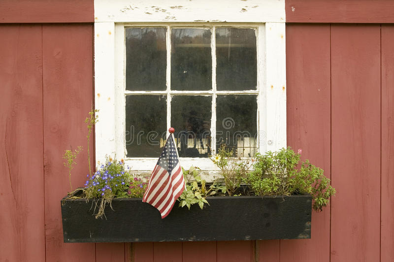 在花盆显示的美国国旗房子窗口曼彻斯特路,圣路易斯县,密苏里 免版税库存照片