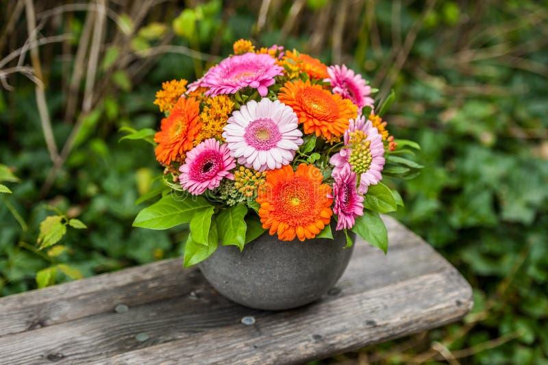 在花盆的美丽的花花束在木长凳 库存图片