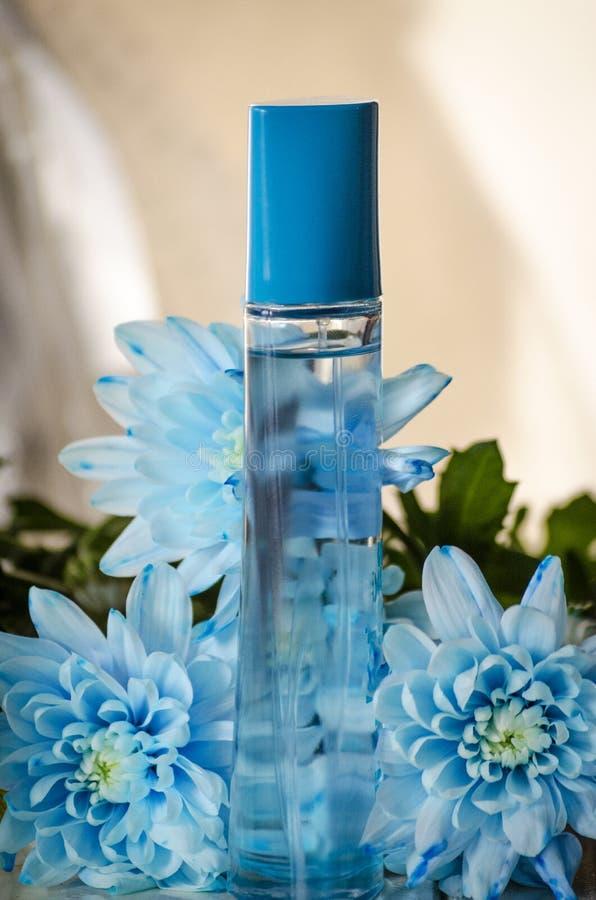 在花背景的香水瓶  库存图片