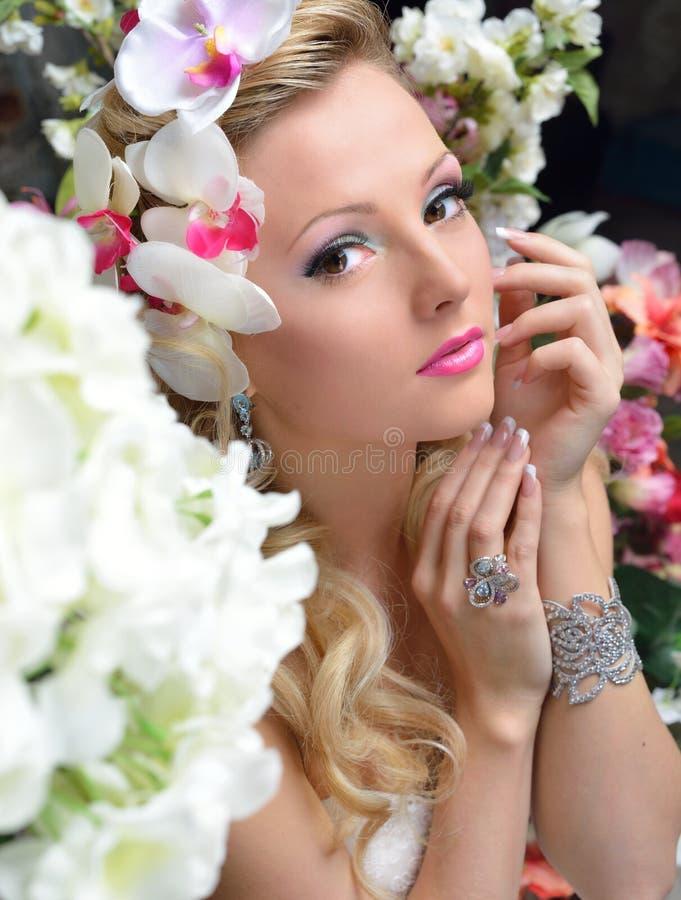 在花附近的美丽的别致的妇女。 免版税图库摄影