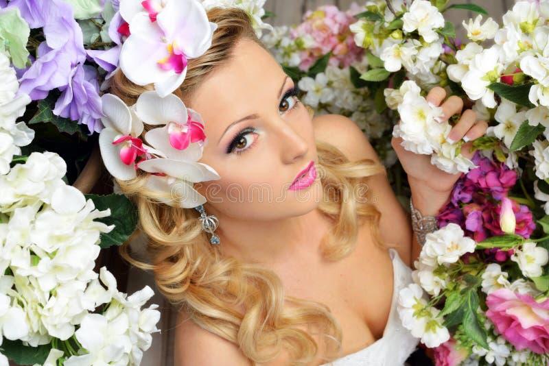在花附近的美丽的别致的妇女。 库存图片