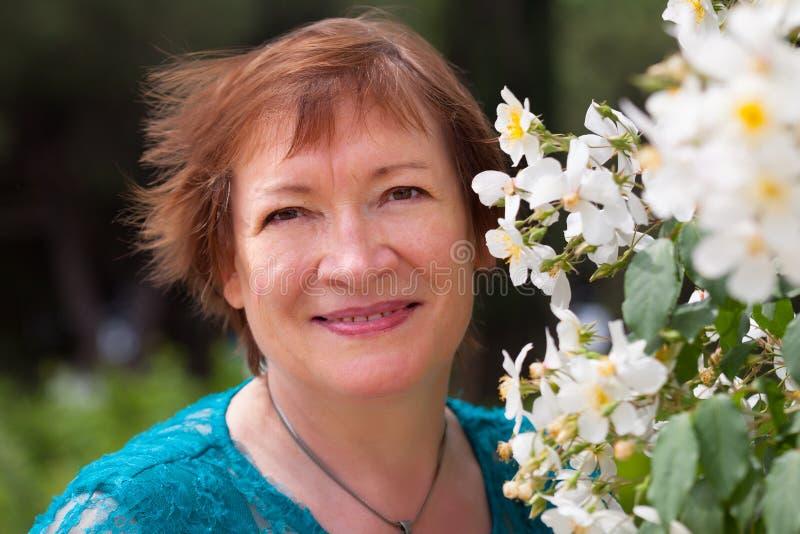 在花附近的逗人喜爱的年长妇女 免版税库存图片