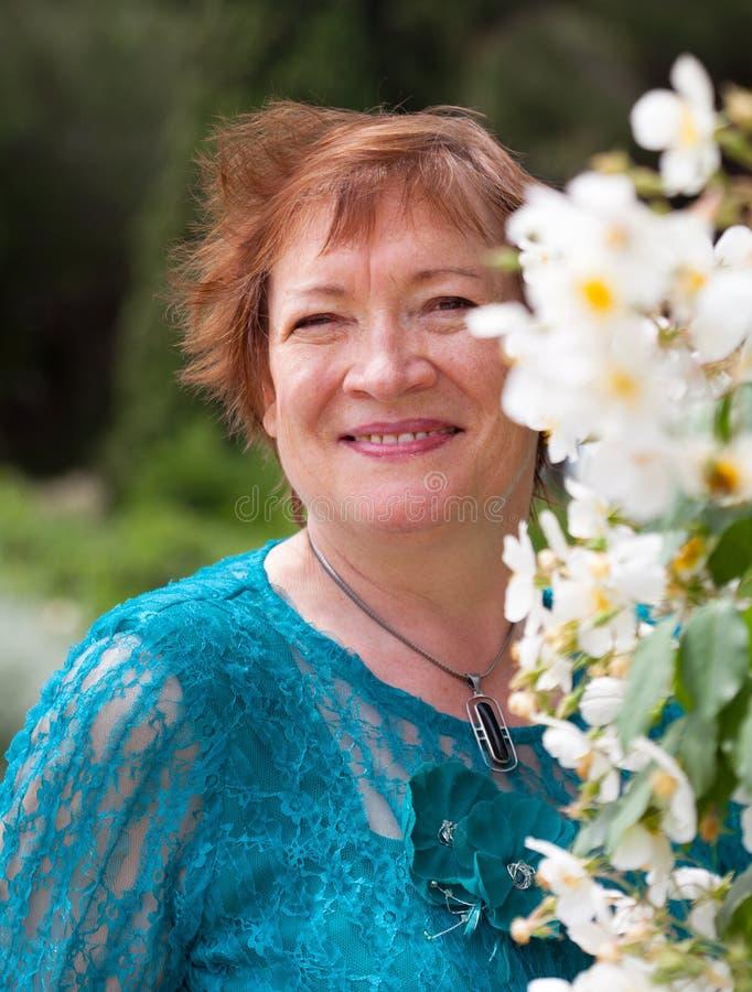 在花附近的年长妇女 免版税库存图片