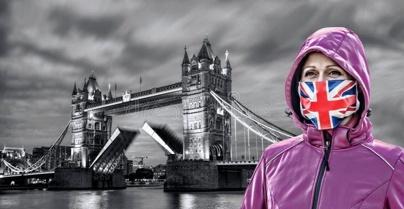 在英国伦敦塔桥前戴着防冠状病毒英国国旗的护面罩的妇女 库存照片