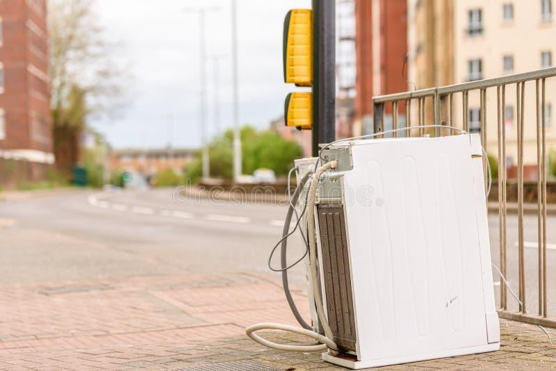 在英国街道路的被放弃的洗衣机或跟斗烘干机 库存照片