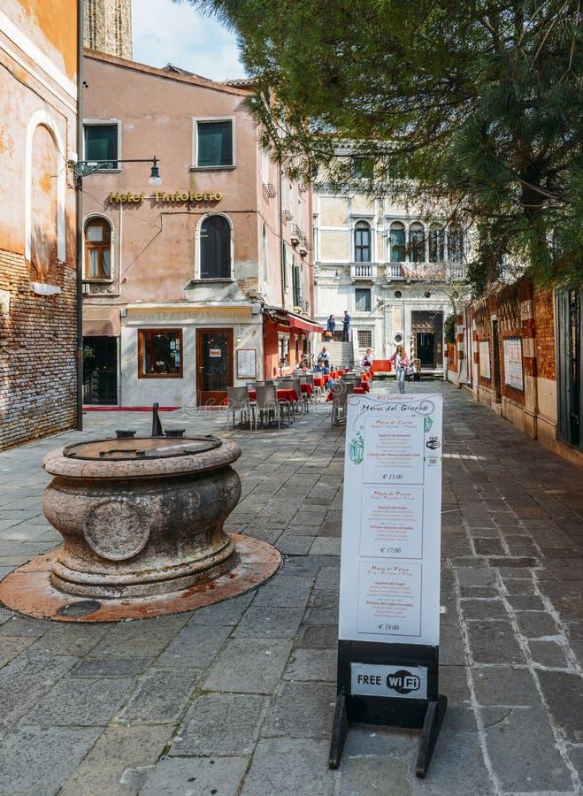 在英语和意大利语的一份菜单在一家餐馆前面在威尼斯的历史的中心 库存图片