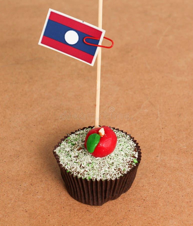 在苹果杯形蛋糕的老挝旗子 库存图片