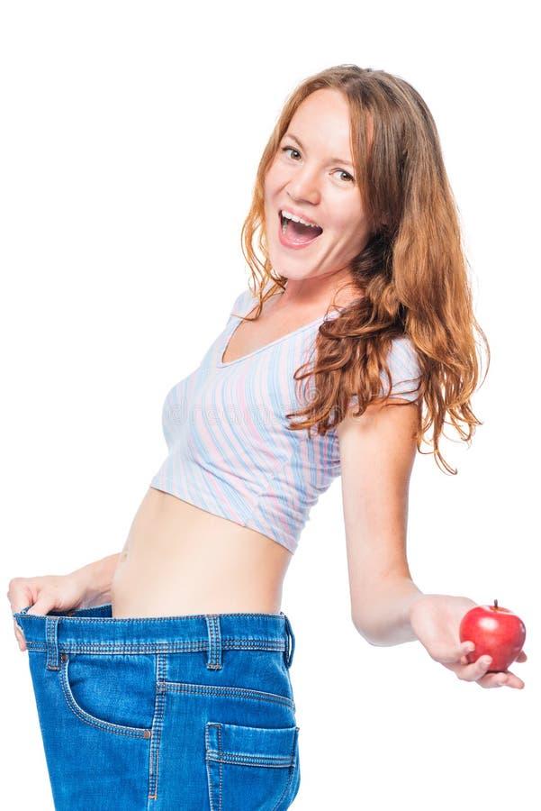 在苹果饮食以后的情感愉快的女孩支持在白色的裤子 库存照片