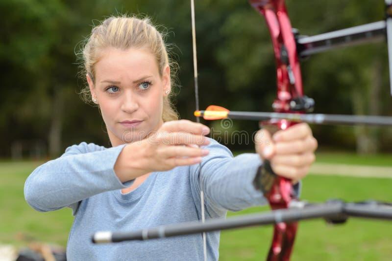 在范围的有吸引力的女性实践的射箭 免版税库存照片