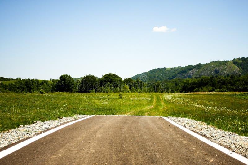 在茫茫荒野中突然结束的柏油路 免版税库存照片