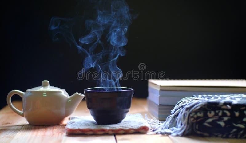 在茶壶和杯子的热的茶在木桌上, 图库摄影