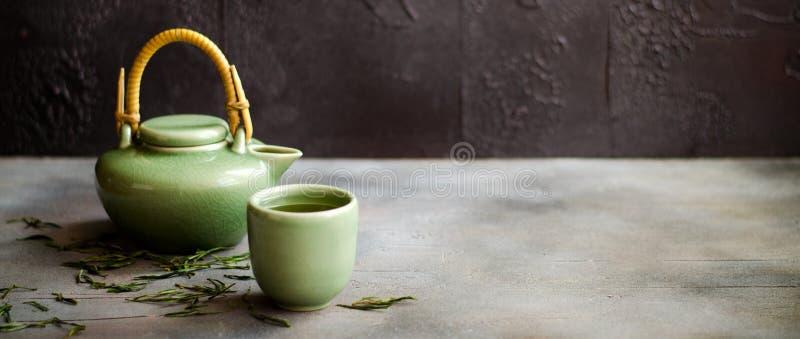 在茶壶的中国绿茶在黑暗的背景 免版税库存照片