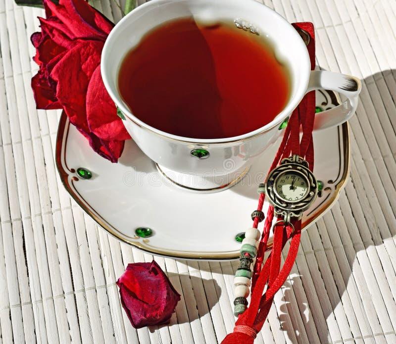 在茶碟上是疏散干燥玫瑰花瓣 有手表在茶杯旁边 库存图片