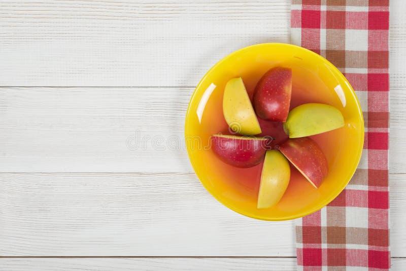在茶碟放置的色的被扎营的苹果 库存图片