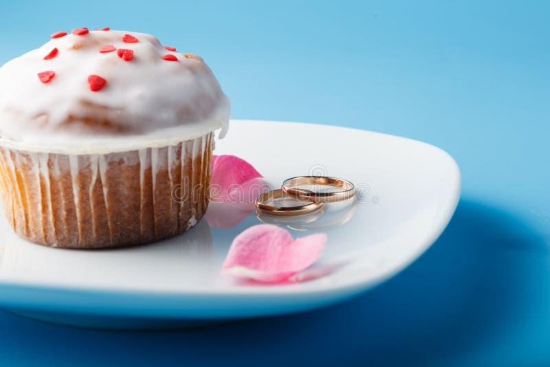在茶碟的五颜六色的松饼有婚戒的 免版税库存照片