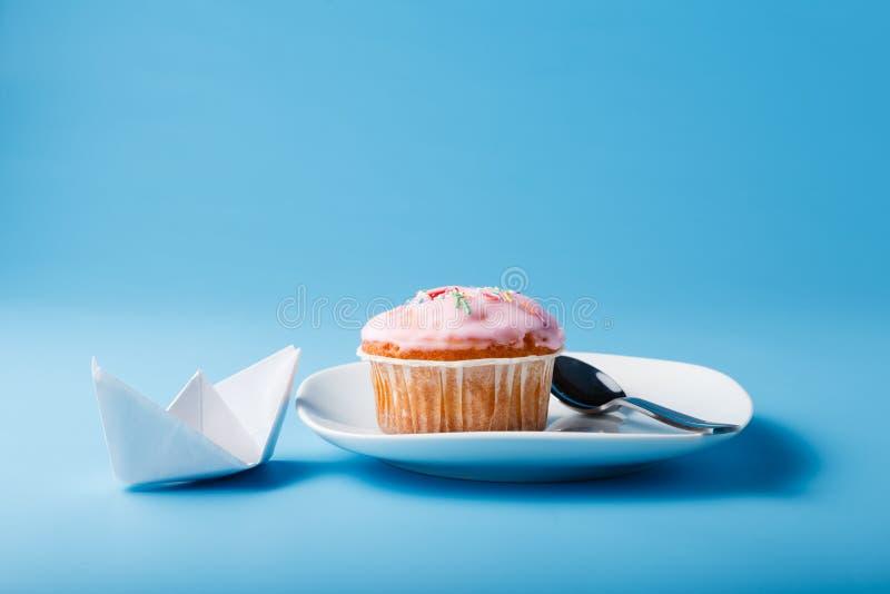在茶碟的五颜六色的松饼有纸小船的 背景看板卡祝贺邀请 图库摄影