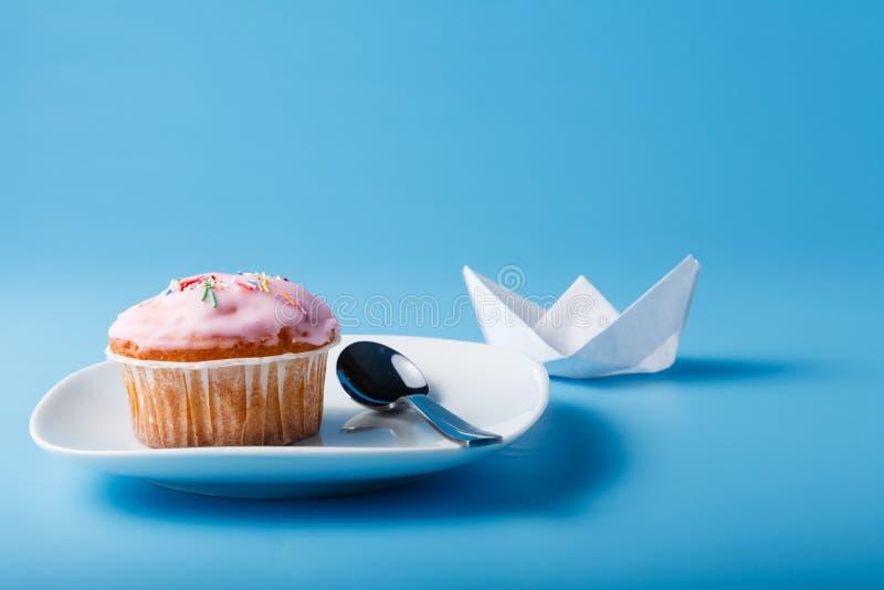 在茶碟的五颜六色的松饼有纸小船的 免版税库存照片
