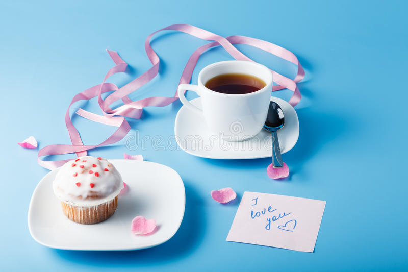 在茶碟的五颜六色的松饼有花瓣和丝带的 免版税库存照片