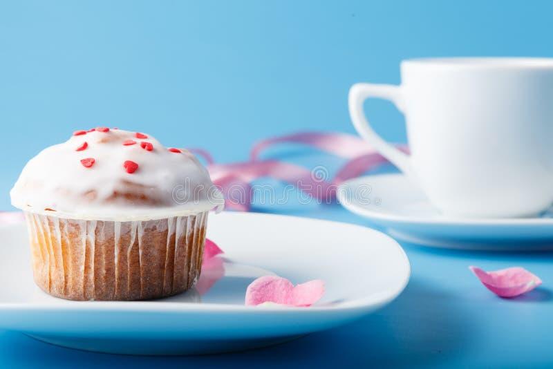 在茶碟的五颜六色的松饼有花瓣和丝带的 免版税图库摄影