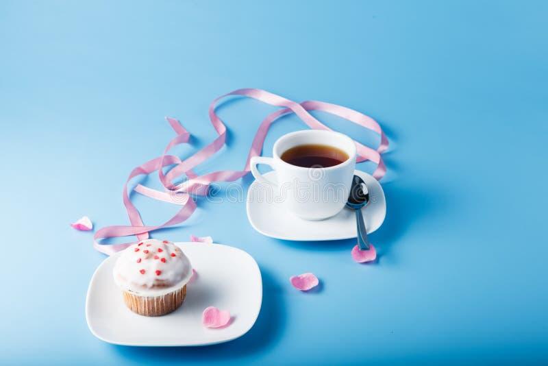 在茶碟的五颜六色的松饼有花瓣和丝带的 库存图片