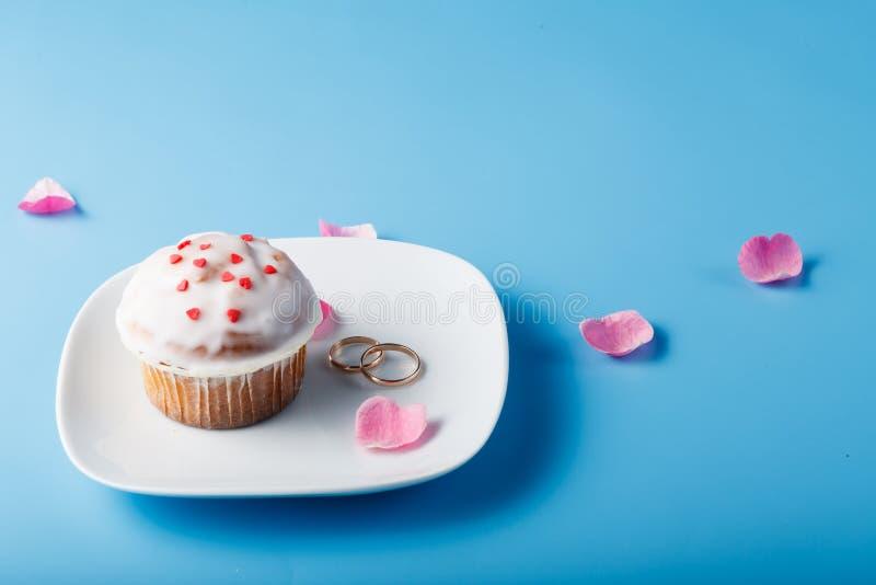 在茶碟的五颜六色的松饼有花瓣和婚戒的 免版税库存照片