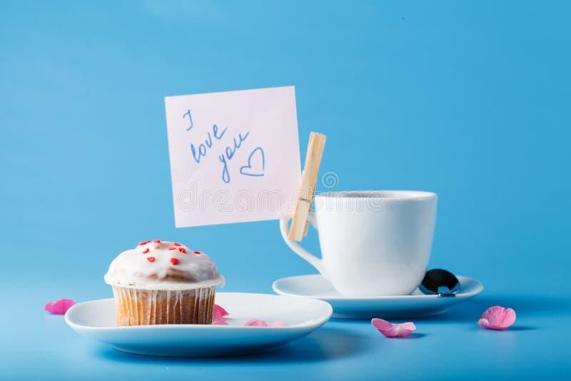 在茶碟的五颜六色的松饼有花瓣和消息的 免版税库存照片