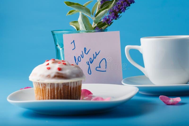 在茶碟的五颜六色的松饼有花瓣和消息的 库存图片