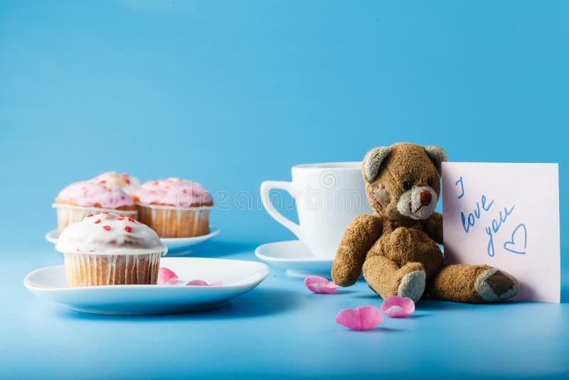 在茶碟的五颜六色的松饼有花瓣和玩具的 免版税库存图片