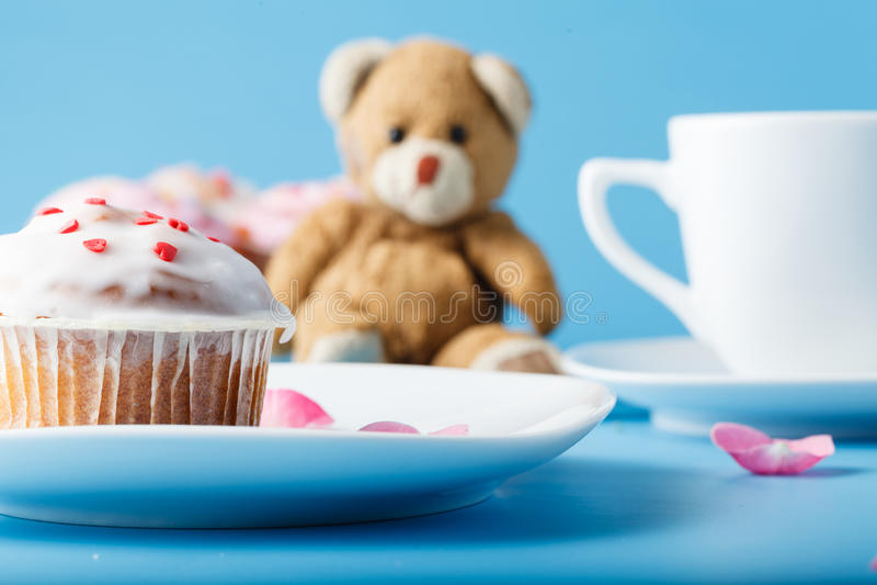 在茶碟的五颜六色的松饼有花瓣和玩具的 库存照片