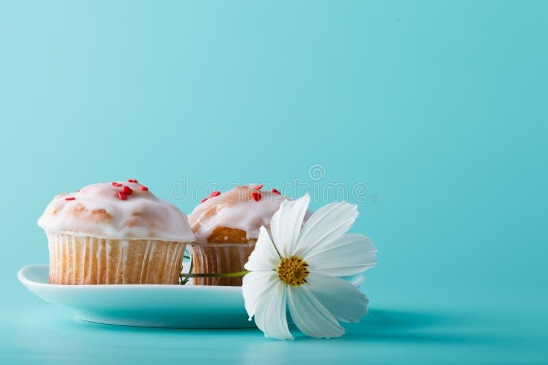 在茶碟的五颜六色的松饼有花的 水色颜色背景 免版税库存图片