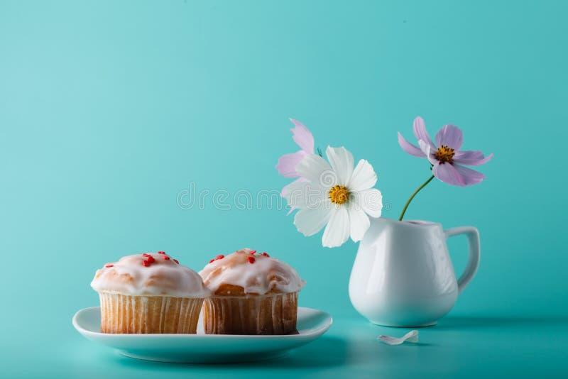 在茶碟的五颜六色的松饼有花的 水色颜色背景 库存照片