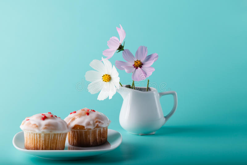 在茶碟的五颜六色的松饼有花的 水色颜色背景 免版税库存照片