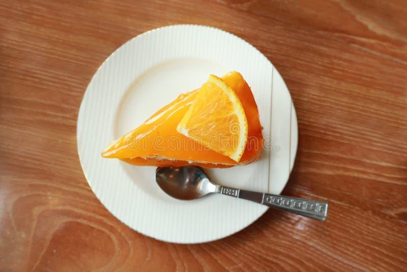 在茶碟的橙色蛋糕在木桌,在饭桌的鲜美甜点心上 免版税库存照片