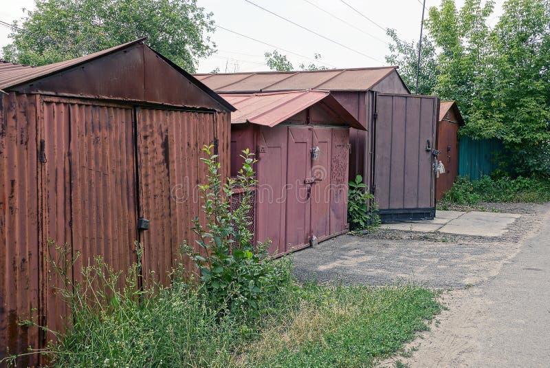 在草丛林的老棕色铁车库在路附近的 免版税库存图片