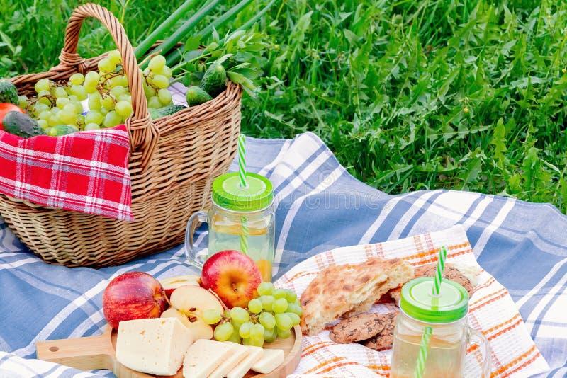 在草在一个夏日-篮子,葡萄,乳酪,面包,苹果的野餐-夏天室外休闲的概念 图库摄影
